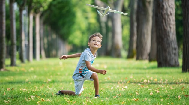 boy-playing-with-toy-glider-in-park-on-summer-day-PTXPHJC