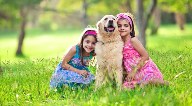 two-young-girls-hugging-golden-retriever-in-the-PZA8LC9