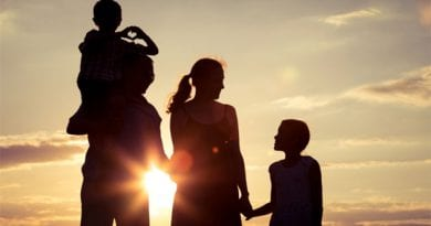 happy-family-standing-on-the-field-at-the-sunset-PPCT7EZ